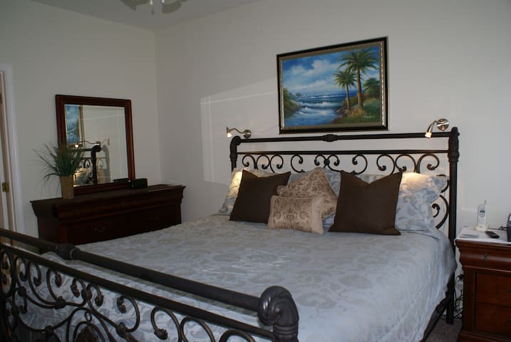 Another look at the lovely master bedroom with king bed, double dresser, reading lights, night stand