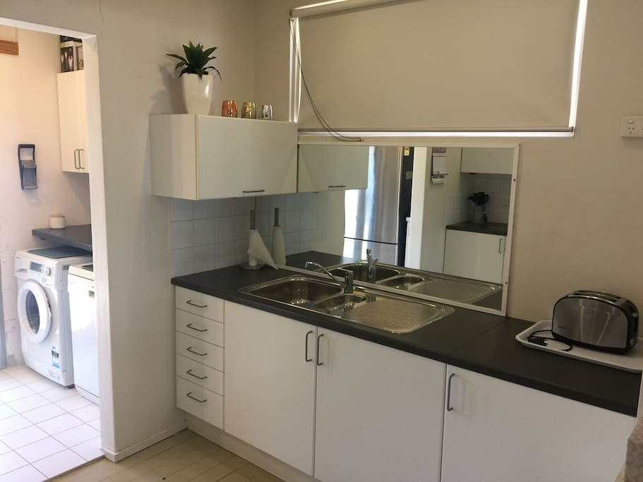 Galley kitchen laundry with dishwasher and front load washing machine