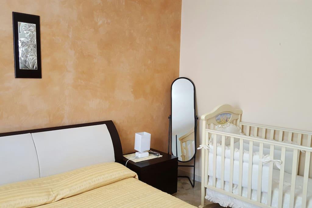Camera con letto matrimoniale e culla