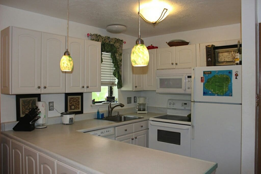 Clean, white kitchen has extraordinary lighting. Fully stocked including appliances, cookware, rice cooker, crock pot, Mr. Coffee, toaster and blender.
