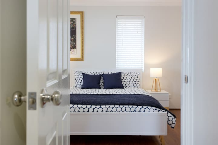 Upstairs main bedroom with queen bed and wardrobe