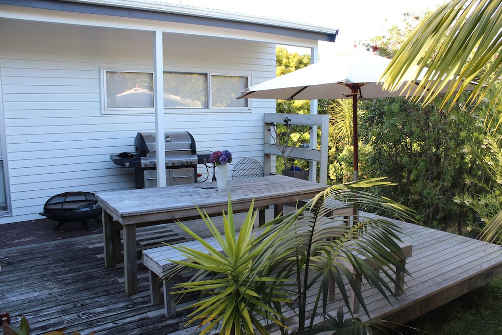 Outdoor entertaining area nestled in amongst a sub-tropical back drop. With BBQ, brazier, outdoor seating and umbrella.
