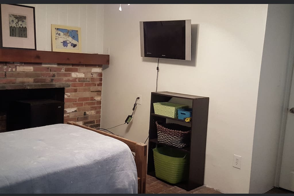 25 inch flat screen tv, a cube frisge nestled in the fireplace with cold water, and a twin bed.