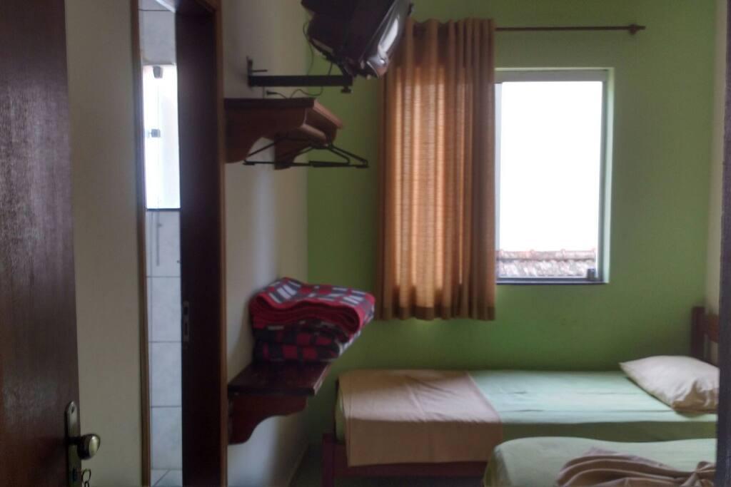 Quarto com Cama de casal e 1 solteiro, banheiro privativo, tv e ventilador.