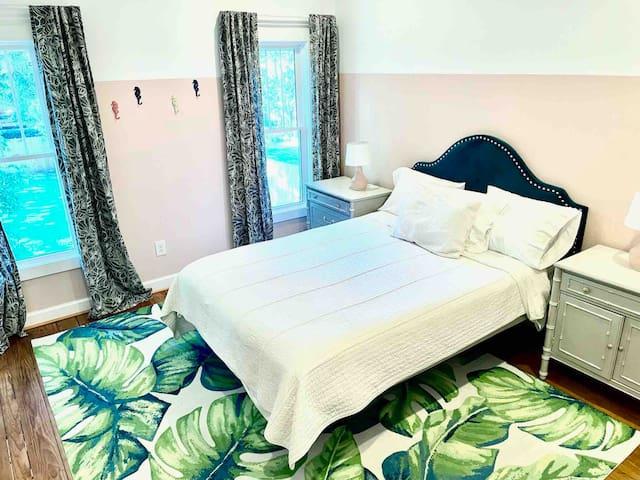 Main bedroom suite with queen Sleep Number bed, en-suite bathroom, TV, and view overlooking private backyard.