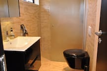 Bathroom with plywood-inspired tiles. Roof and hand shower. Wall mounted toilet. Floor heating with individual thermostats for each room gives pleasant warm floors  during cold periods.