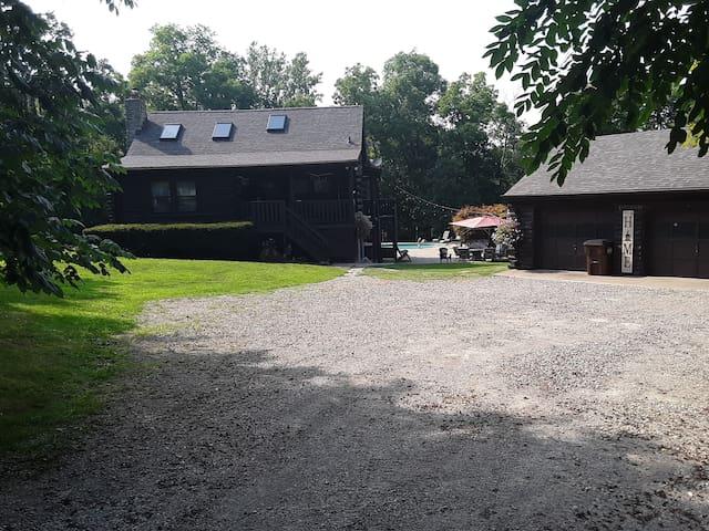Log cabin with seasonal inground pool and hot tub.