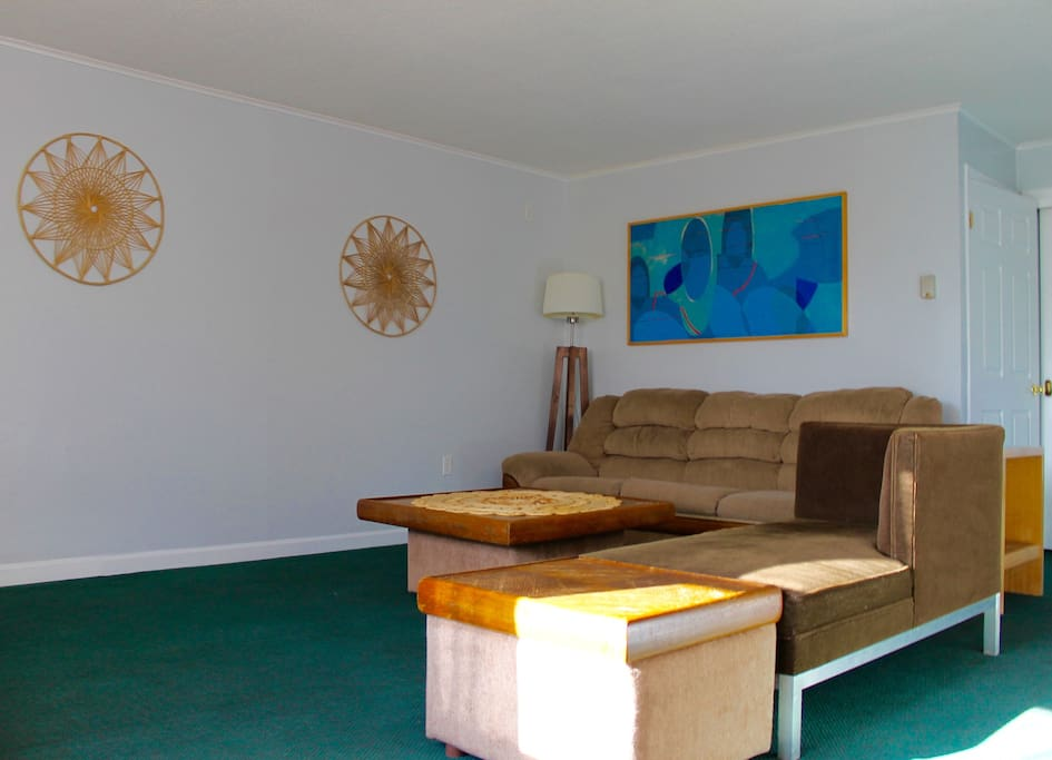 The well-lit and spacious living room features plenty of seating and a television.