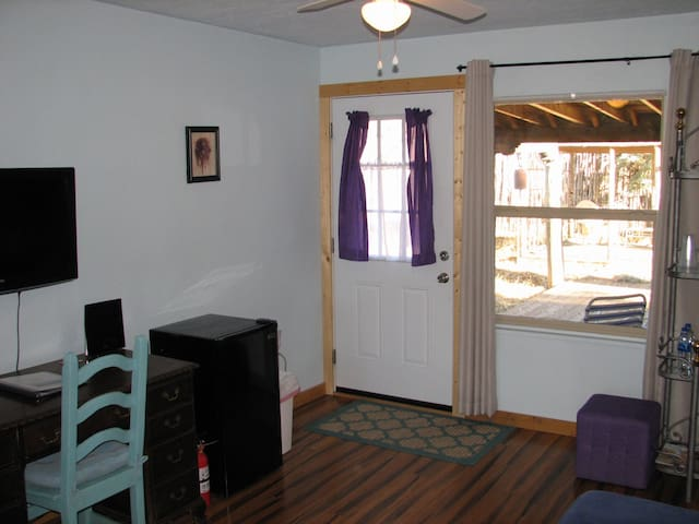 Entryway, refrigerator, desk and chair.