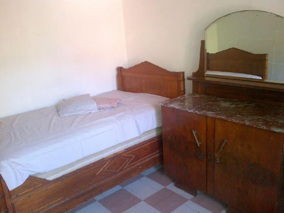 Chambre avec 2 lits simples et une commode