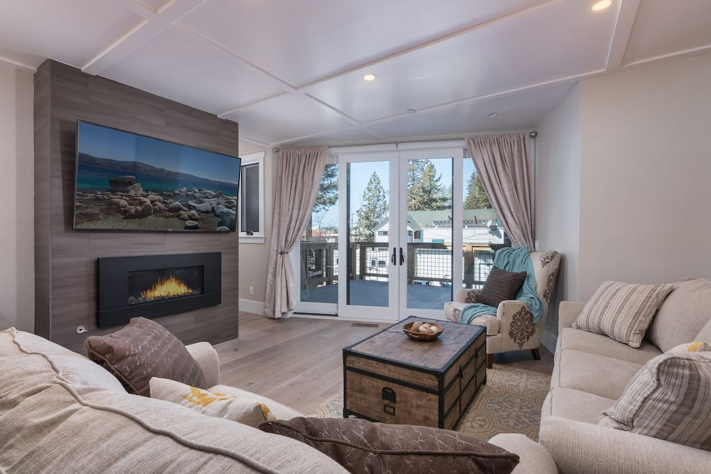 """The living room has a 65"""" smart TV over a gas fireplace"""