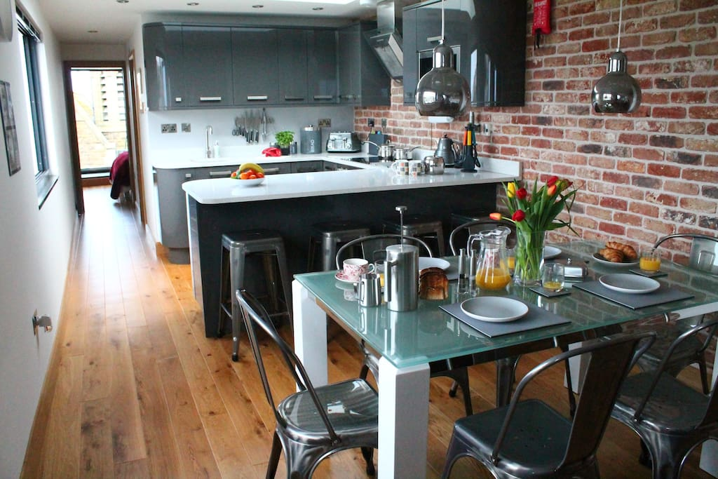Open planned kitchen with bar stools & dining table in the foreground.