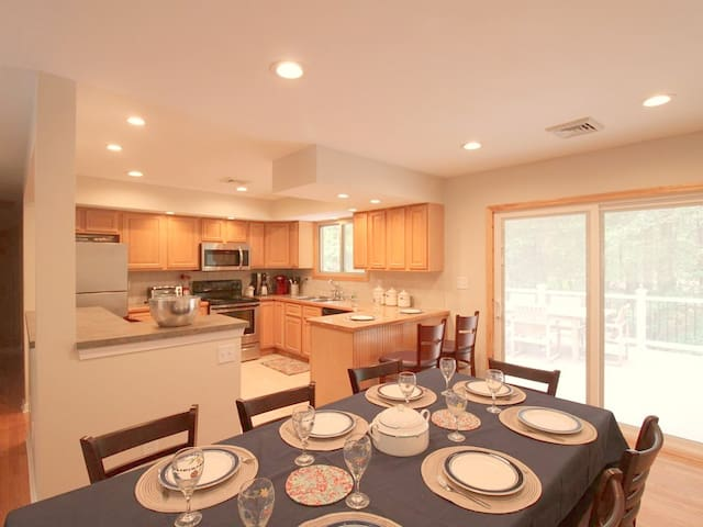 Dining area and kitchen with sliding door to large deck area