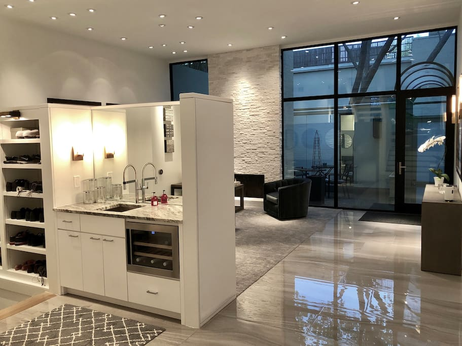 Wet Bar/Entry/Foyer with floor to ceiling windows showing the private front courtyard.
