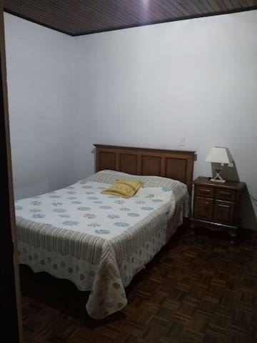 La habitación tiene una cama matrimonial, una lámpara y closet con espacio