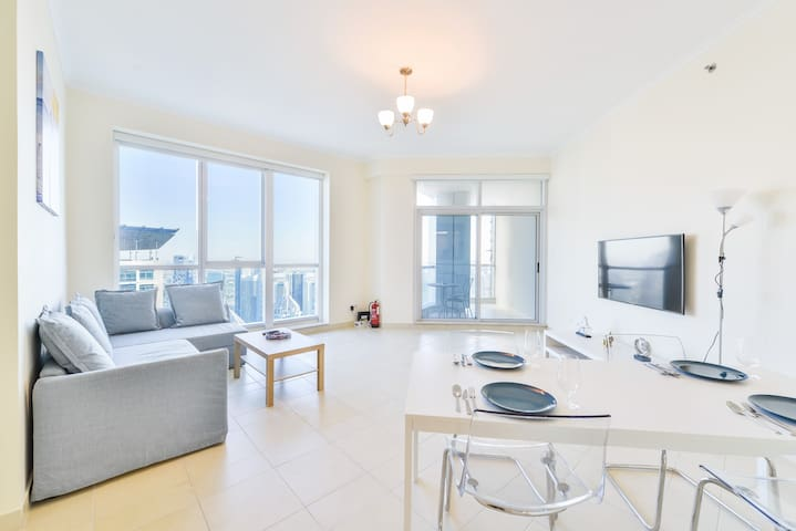 Clean and airy living room with bird's-eye views of Dubai Marina, access to a private patio, a 6-person dining area, a cozy rest area, a 55 inch Smart TV and 250 MB high speed internet