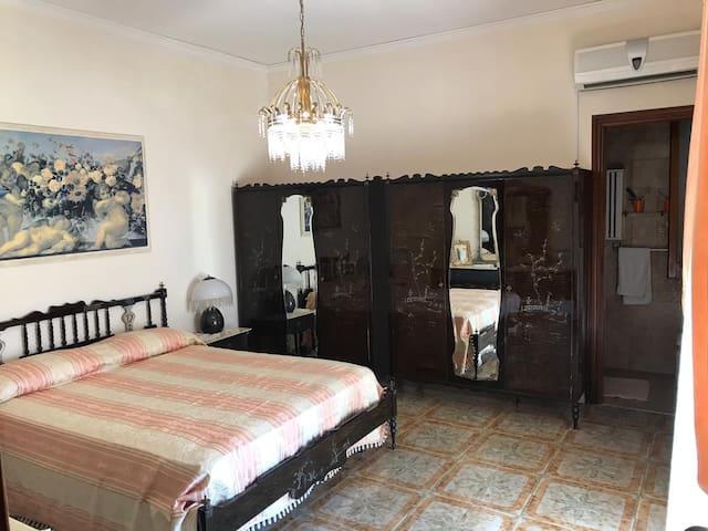 Camera da letto con letto matrimoniale, bagno privato, balcone su giardino e aria condizionata