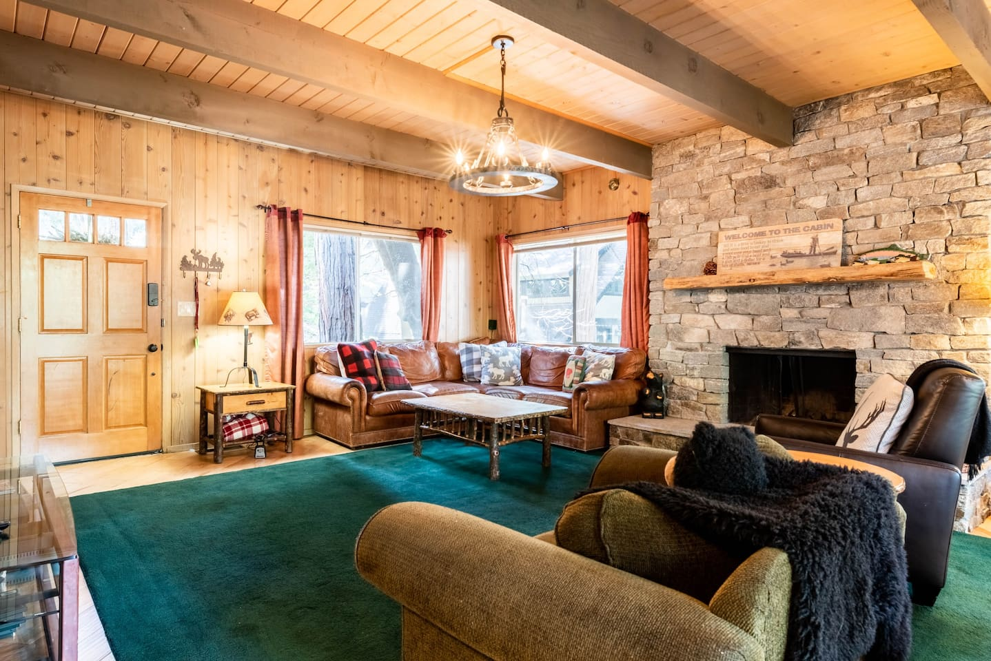 Our comfortable living room features an oversized couch, wood beams, and stone fireplace.