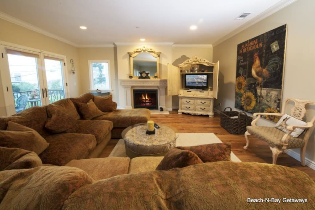 This comfortable living room includes a flat screen TV, DVD player, and a gas fireplace