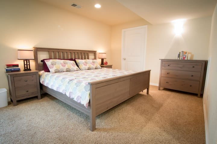 Bedroom area with king-sized bed, dresser, and 2 nightstands