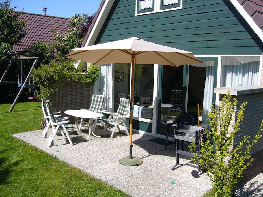 Terrace with garden furniture, a parasol, a barbecue and a swing for children