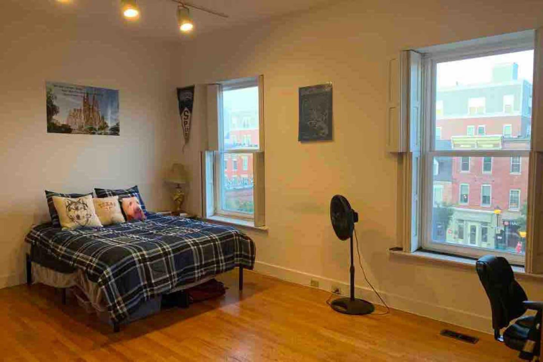 Bedroom 1: 18'x14' with open windows overlooking Broadway Market. Chair is where desk begins.