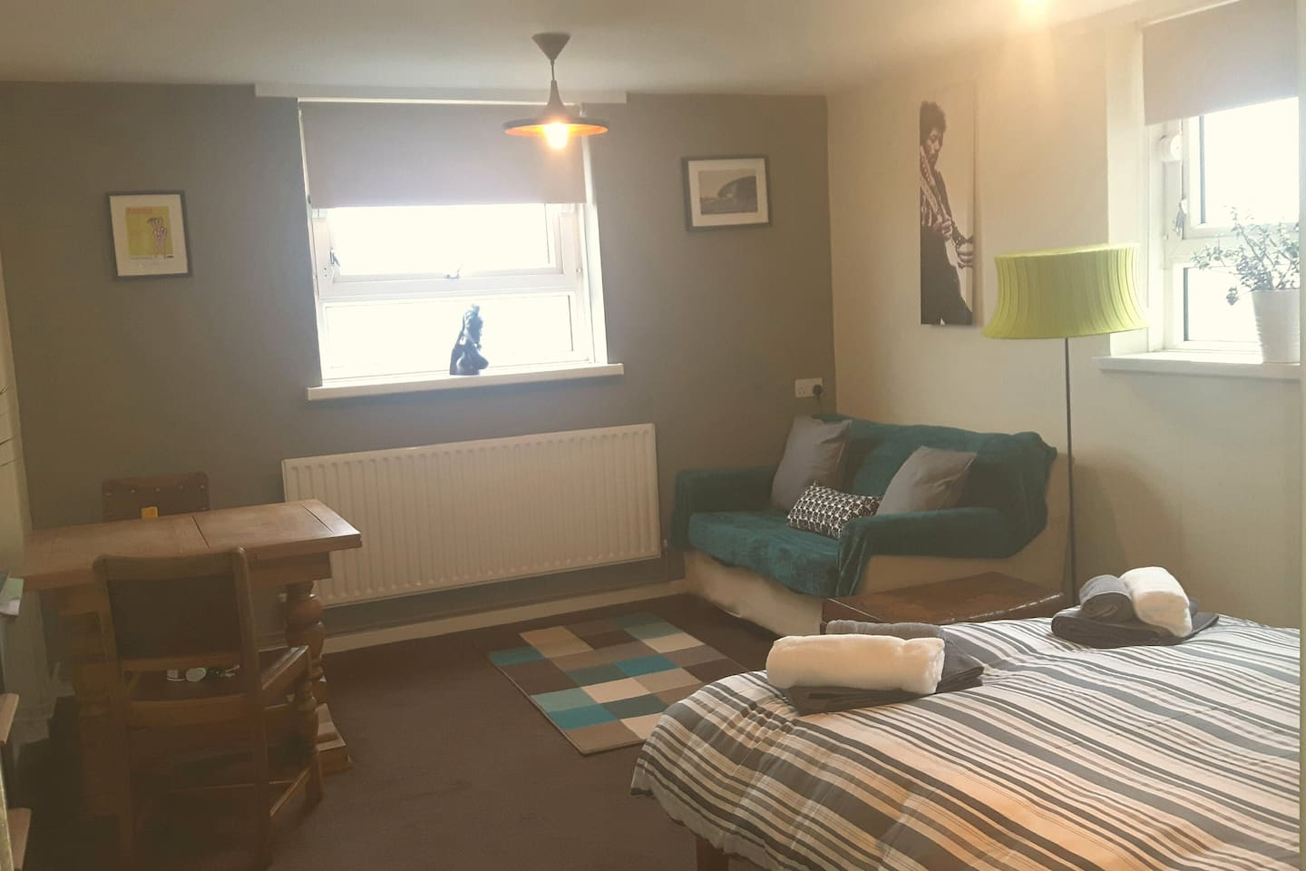 Spacious living area with double bed and two seater sofa bed & dining table.