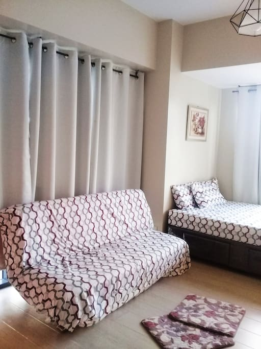 queen size bed with a sofa bed beside n 2 extra roll on floor matress