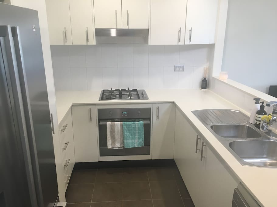 Modern kitchen with dishwasher, fridge/freezer, oven, cooktop, microwave, toaster and sink area