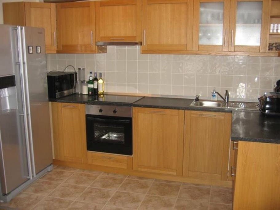 Fully equipped kitchen with oven, dishwasher, microwave and american fridge with ice dispenser.