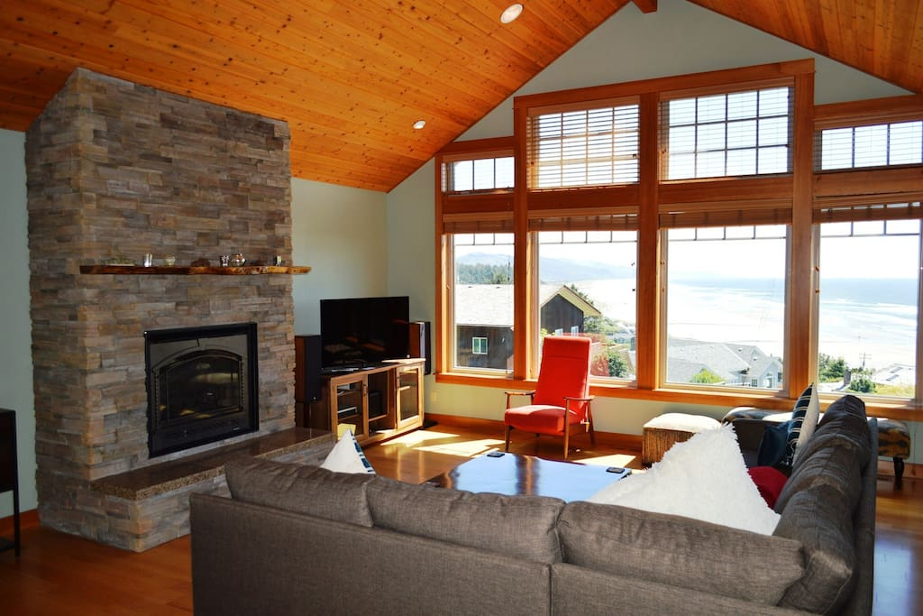 Upper entry level living room with a Flat screen cable TV/DVD, Apple TV, surround sound, gas fireplace, large sectional couch, two arm chairs, two bench seats, record player w/ records, door to deck and large picture windows with spectacular ocean views