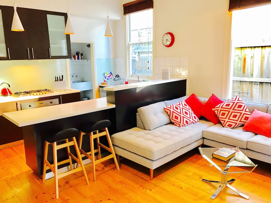 Bright and cheerful open-plan living with a super comfy couch and handy breakfast bar.