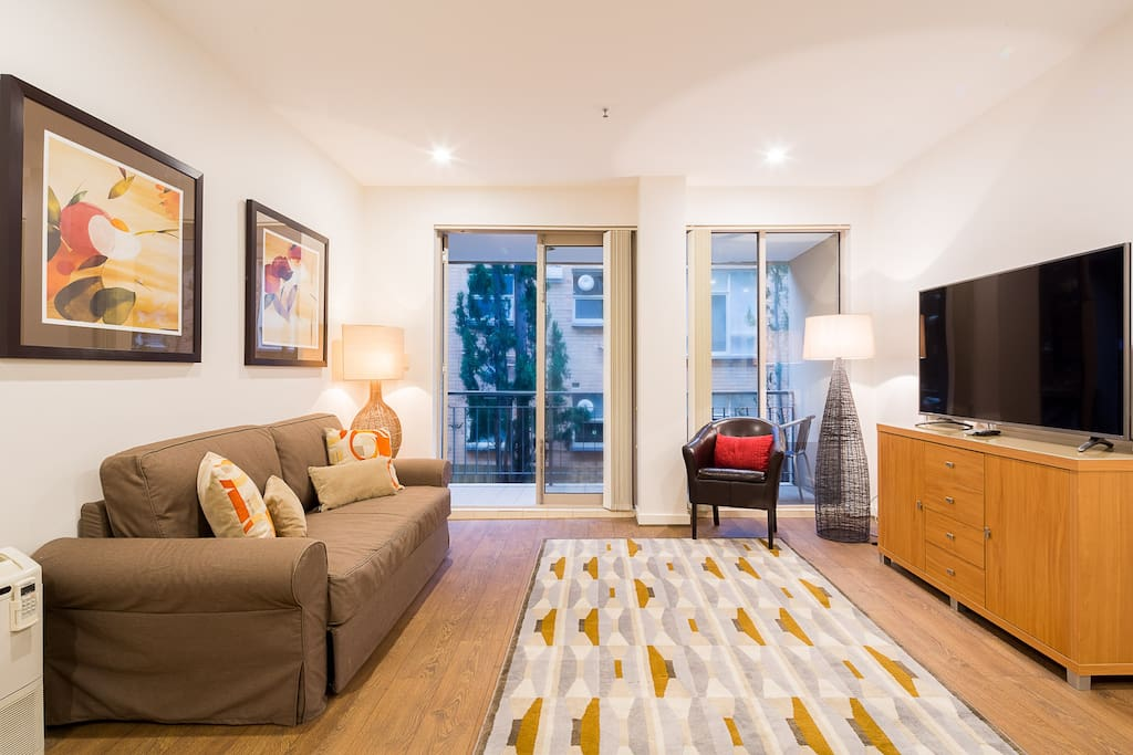 "Comfortable living room with a double size sofa bed and 58"" UHD Smart TV in this 1-bedroom StayCentral St Kilda Serviced Apartment"