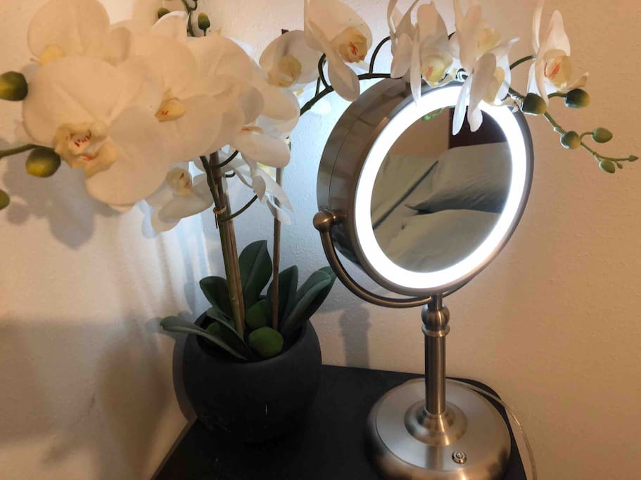 the comfy queen bed is reflected in the vanity mirror with LED light