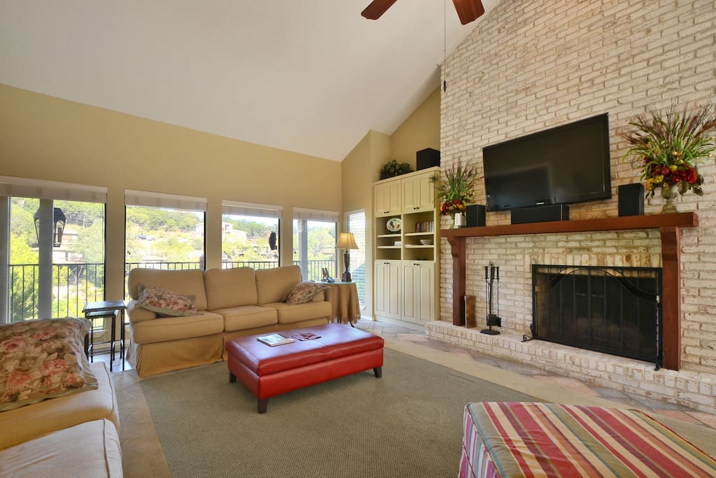 "Huge living area with fireplace, 52"" flatscreen TV with surround sound, two couches and chair with ottoman"