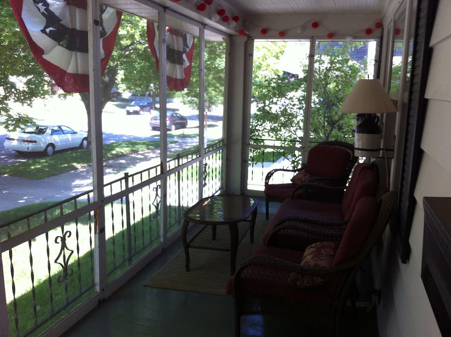 View of screened-in front porch from front door. Lamps on side of house can be used for reading or you can plug in red lanterns along porch ceiling for cozy lighting.