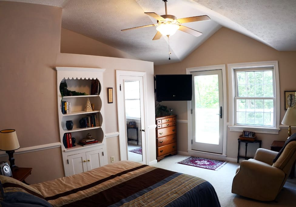 Airy vaulted ceiling room with balcony overlooking the forest.  Features ceiling fan, swiveling flat-screen tv with basic cable,  Books, recliner, dresser & closet, clock radio with nature sounds and cd player, and full-size bed.