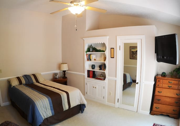 Airy vaulted-ceiling room with balcony overlooking the forest.  Features ceiling fan, swiveling flat-screen tv with basic cable,  Books, recliner, dresser & closet, clock radio with nature sounds and cd player, and full-size bed.