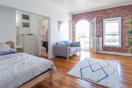 This modern studio is a steal. You get AC, a brick wall, balcony with a view, a pool, 100% natural light, and an apt that is beautiful. Styled as a chic old style Hollywood hotel room, you get way more for the price of less. Ask questions!