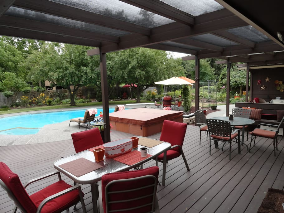 Expansive covered deck and pool side  seating options offer plenty of spaces to enjoy the private back yard.