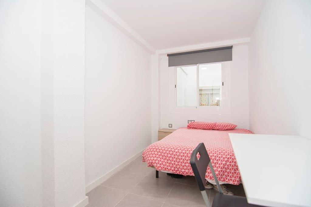 Habitación con cama de matrimonio, luminosa, cuenta con armario, escritorio, mesita y su propia llave.