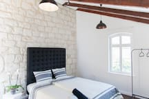 the master bedroom with the renovated original stone wall background
