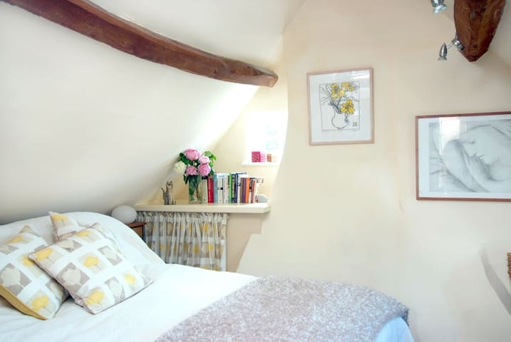 A lovely country bedroom with a bed dressed in cotton bedlinen - and sprting down and a down and feather quilt and pillows (there are also synthetic alternatives)