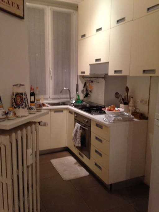 Open/ separate kitchen with stove top and oven, full size fridge, dishes, pots and pans, and a window