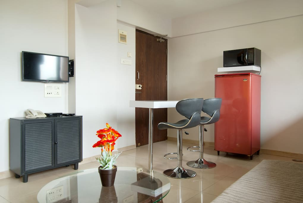 View of flat screen TV, refrigerator & eat-in kitchen dining counter