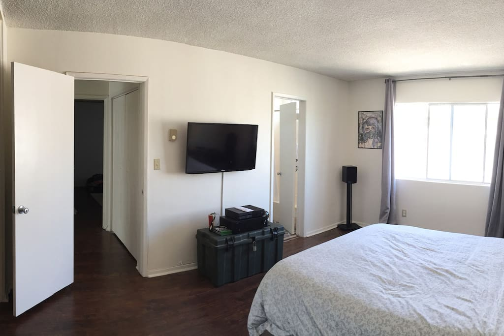 A view of the bedroom from the opposite side, including the bathroom.