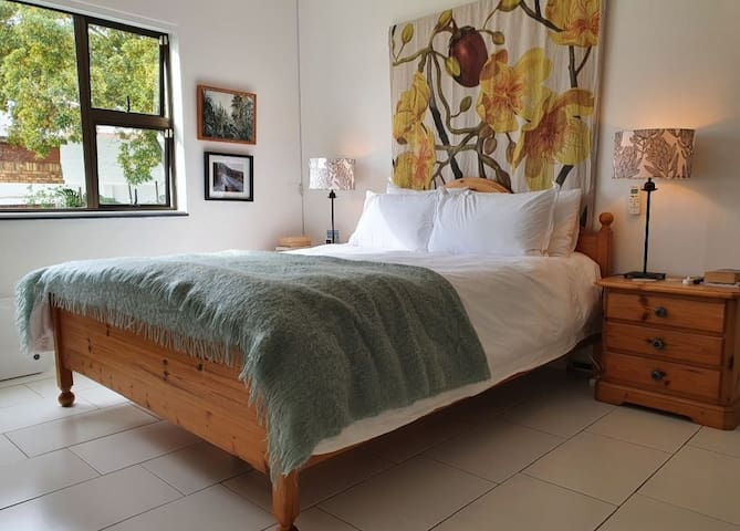 Main bedroom with queen bed, Air Conditioning, and en suite with a door that opens up to the backyard