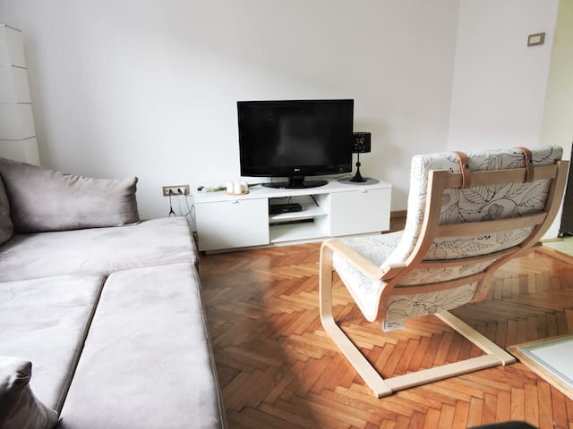 Cosy living room with comfortable sofa and chair to lounge. Flatscreen TV and Cable. Air Conditioning and Heating.