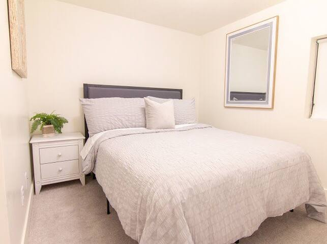 Cozy 2nd bedroom with queen bed and large closet found on the ground floor.