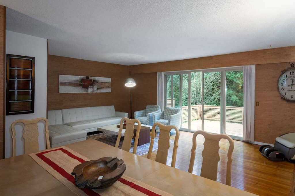 Large living space, with 8 person dining table, looking out to large deck and garden